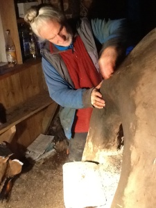 Danny using only a silica stone and water to repair cracks in the clay oven in preparation for Sunday's gathering.
