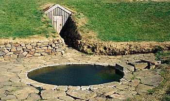 The photo to the left shows the bath built by Snorri Sturluson at his farm at Reykholt, around the year 1210. It's fed by water piped from separate hot and cold water springs, so the temperature can be adjusted to suit. The door in the hillside behind the bath leads to a tunnel which probably led back to Snorri's farmhouse.